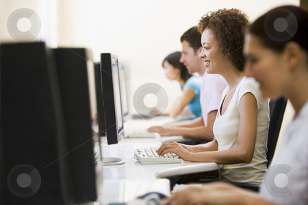 Four people in computer room typing and smiling stock photo,  by Monkey Business Images