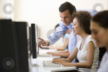 Man assisting woman in computer room stock photo,  by Monkey Business Images