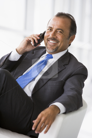 Businessman talking on mobile phone stock photo, Businessman talking on mobile phone in lobby by Monkey Business Images