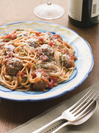Spaghetti Meatballs in Tomato sauce with Parmesan stock photo, Plate of Spaghetti Meatballs in Tomato sauce with Parmesan with cutlery and wine by Monkey Business Images