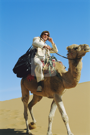 Man with mobile phone riding camel in desert stock photo,  by Monkey Business Images