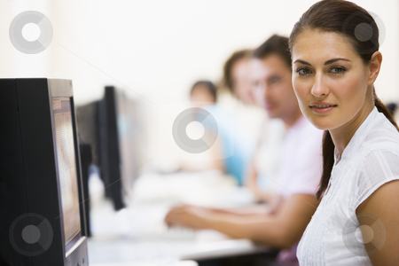 Woman sitting in computer room with people in background stock photo,  by Monkey Business Images