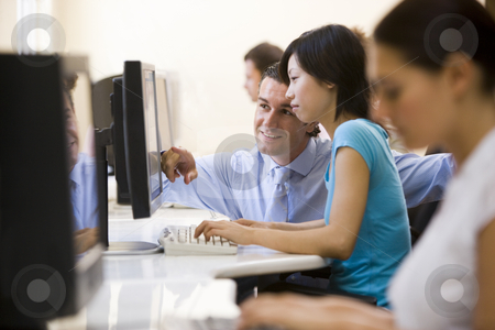 Man assisting woman in computer room smiling stock photo,  by Monkey Business Images