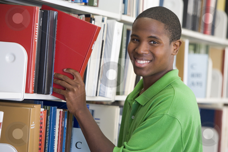 University student choosing book in library stock photo, Male student selecting book in library by Monkey Business Images