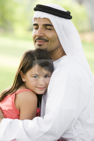 A Middle Eastern man and his daughter sitting in a park stock photo,  by Monkey Business Images