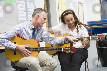 Schoolgirl and teacher playing guitar in music class stock photo,  by Monkey Business Images