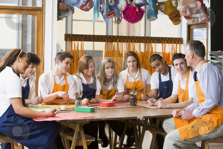 Schoolchildren and teacher sitting around a table in art class stock photo,  by Monkey Business Images
