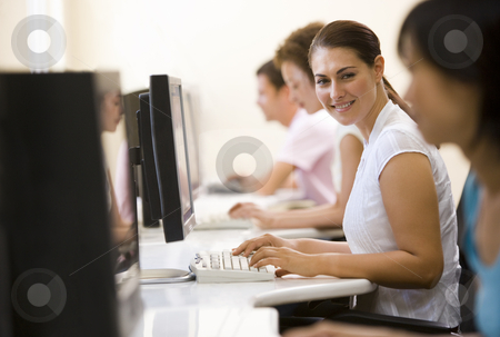 Four people sitting in computer room typing and smiling stock photo,  by Monkey Business Images