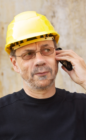 Yellow hard hat stock photo, Mature man in yellow hard hat speaking on mobile phone by Mikhail Lavrenov