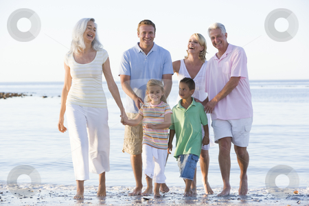 Extended family at the beach smiling stock photo,  by Monkey Business Images