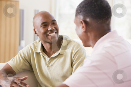 Two men in living room talking and smiling stock photo,  by Monkey Business Images