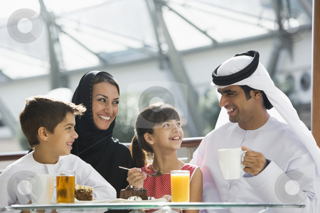 A Middle Eastern family enjoying a meal in a restaurant stock photo,  by Monkey Business Images