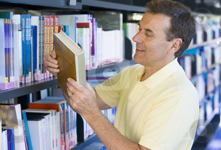 Man in a library reading book cover stock photo,  by Monkey Business Images