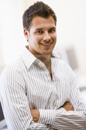 Man standing in computer room smiling stock photo,  by Monkey Business Images