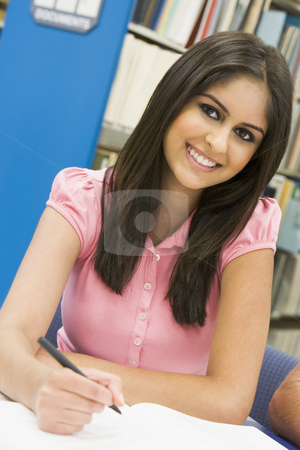 University student working in library stock photo, Female student writing report in library by Monkey Business Images