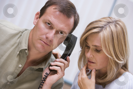 Couple receiving bad news over phone stock photo, Couple receiving bad news over the phone at home by Monkey Business Images