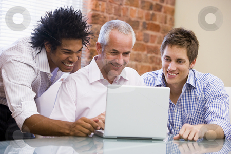 Three businessmen sitting in office with laptop smiling stock photo,  by Monkey Business Images