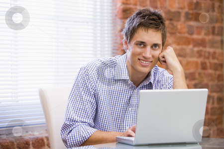 Businessman sitting in office with laptop smiling stock photo,  by Monkey Business Images