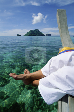 Man on pier dangling feet over clear water stock photo,  by Monkey Business Images