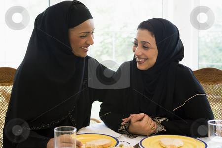 Two Middle Eastern women enjoying a meal in a restaurant stock photo,  by Monkey Business Images