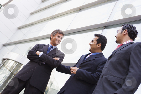 Group of businessmen outside office building stock photo, Group of businessmen outside modern office building by Monkey Business Images