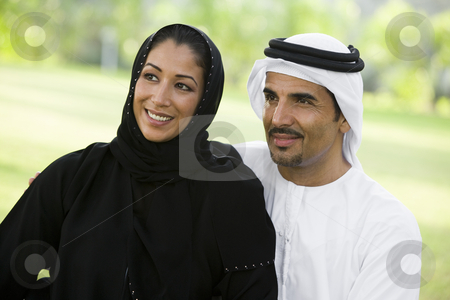 A Middle Eastern couple sitting in a park stock photo,  by Monkey Business Images