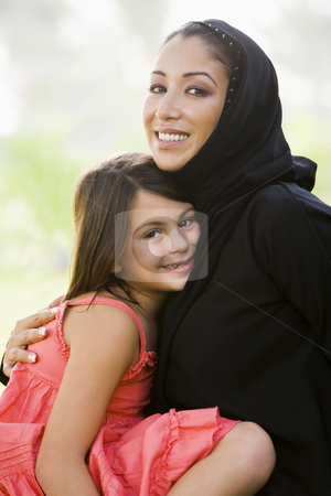 A Middle Eastern woman and her daughter sitting in a park stock photo,  by Monkey Business Images