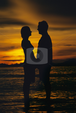 Silhouette of couple standing face to face on beach at sunset stock photo,  by Monkey Business Images