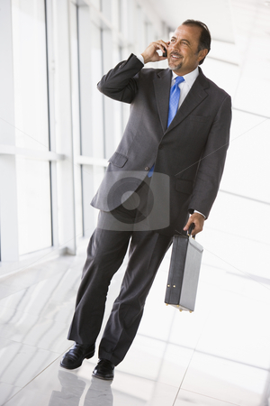 Businessman talking on mobile phone in lobby stock photo, Businessman talking on mobile phone in office lobby by Monkey Business Images