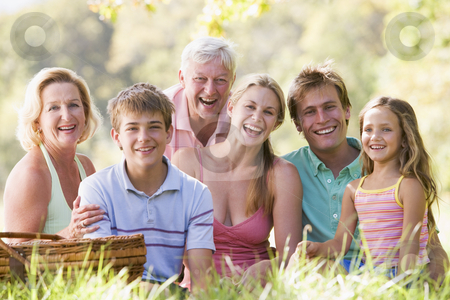 Family at a picnic smiling stock photo,  by Monkey Business Images