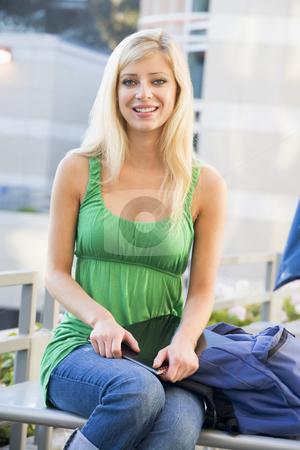 Female student sitting outside stock photo, Female university student working outside by Monkey Business Images