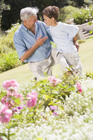 Grandfather and grandson outdoors in garden talking and smiling stock photo,  by Monkey Business Images