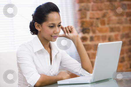 Businesswoman in office with laptop stock photo,  by Monkey Business Images
