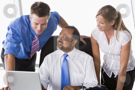 Group of business people working in office stock photo, Group of business people working in office looking at laptop by Monkey Business Images