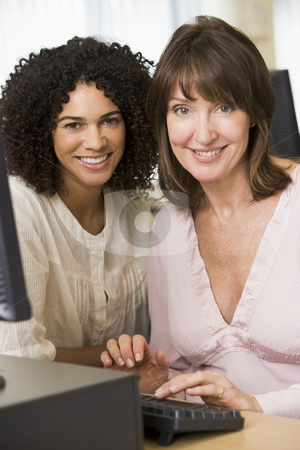 Two female adult students working on a computer together stock photo,  by Monkey Business Images