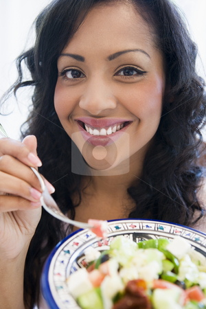 A South American holding a salad up to the camera stock photo,  by Monkey Business Images