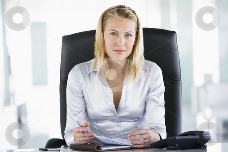 Businesswoman sitting in office with personal organizer stock photo,  by Monkey Business Images