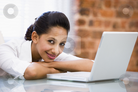 Businesswoman in office with laptop smiling stock photo,  by Monkey Business Images