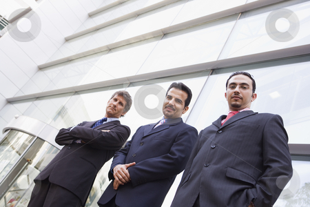 Group of businessmen outside office building stock photo, Group of businessment outside modern office building by Monkey Business Images
