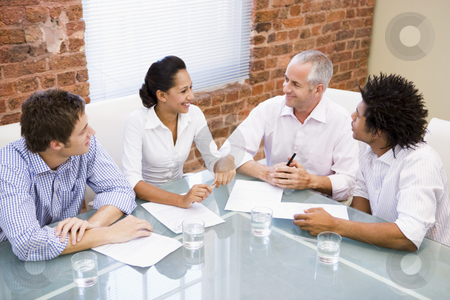 Four businesspeople in boardroom smiling stock photo,  by Monkey Business Images