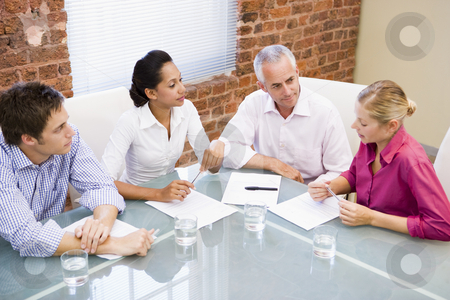 Four businesspeople in boardroom talking stock photo,  by Monkey Business Images