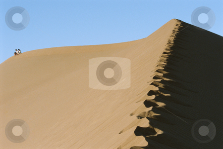 Two people riding a camel across desert, hoofprints in foregroun stock photo,  by Monkey Business Images
