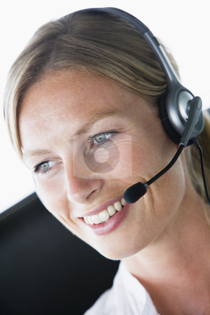 Businesswoman in office wearing headset and smiling stock photo,  by Monkey Business Images