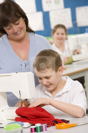 Teacher and schoolboy using a sewing machine in sewing class stock photo,  by Monkey Business Images