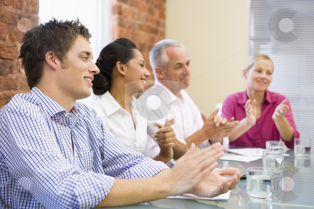 Four businesspeople in boardroom applauding and smiling stock photo,  by Monkey Business Images