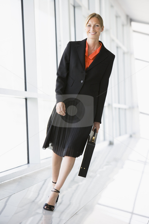 Businesswoman walking in corridor smiling stock photo,  by Monkey Business Images