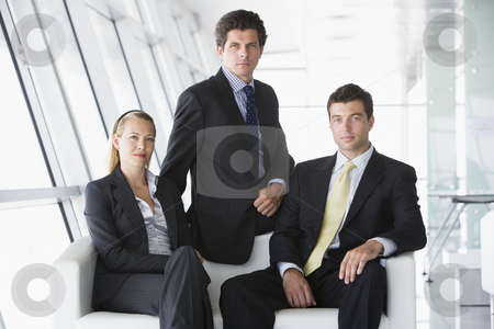 Three businesspeople sitting in office lobby stock photo,  by Monkey Business Images