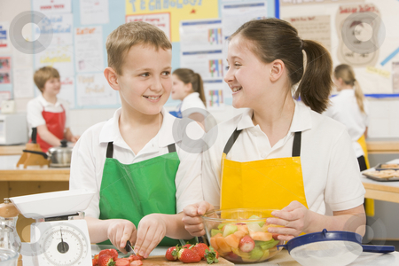 Schoolchildren at school in a cooking class stock photo,  by Monkey Business Images