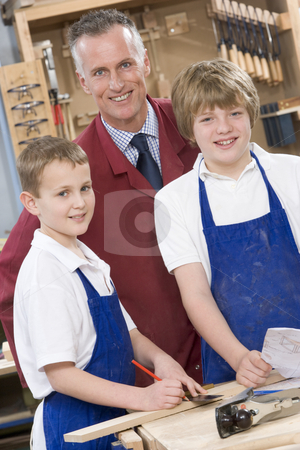 Schoolboys and teacher in woodwork class stock photo,  by Monkey Business Images