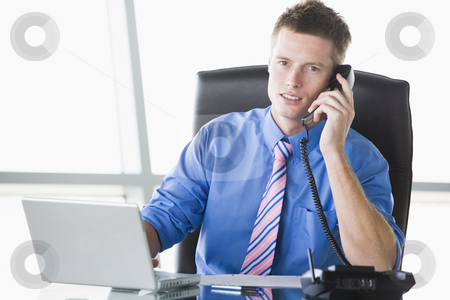Businessman sitting in office with laptop using telephone stock photo,  by Monkey Business Images
